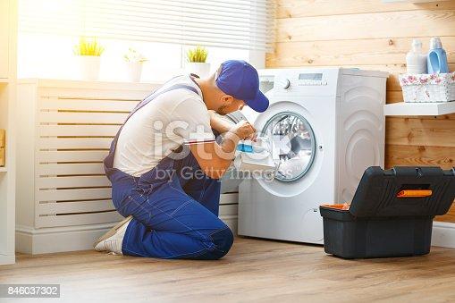 istock working man   plumber repairs  washing machine in   laundry 846037302
