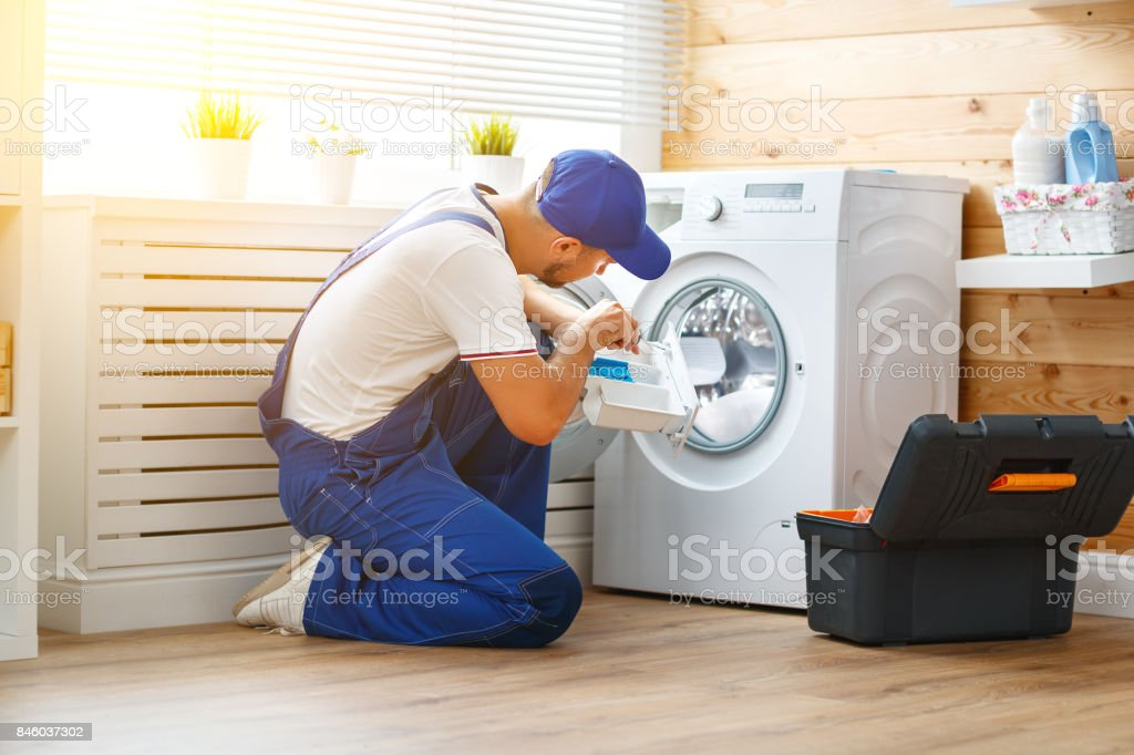 working man   plumber repairs  washing machine in   laundry stock photo
