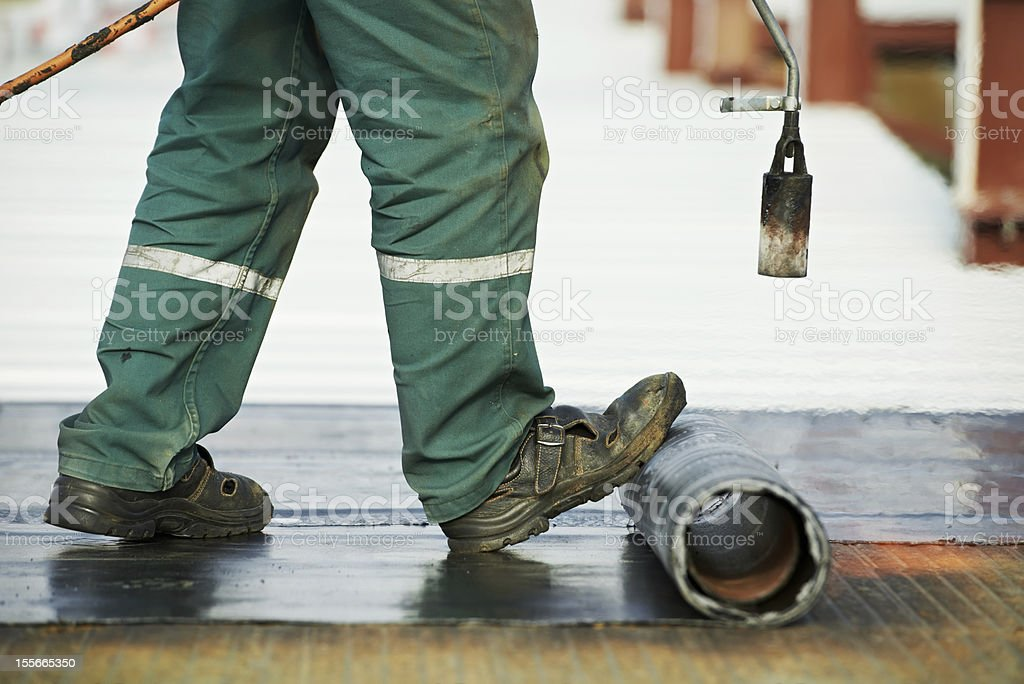 Working man rolling out black shiny mats stock photo