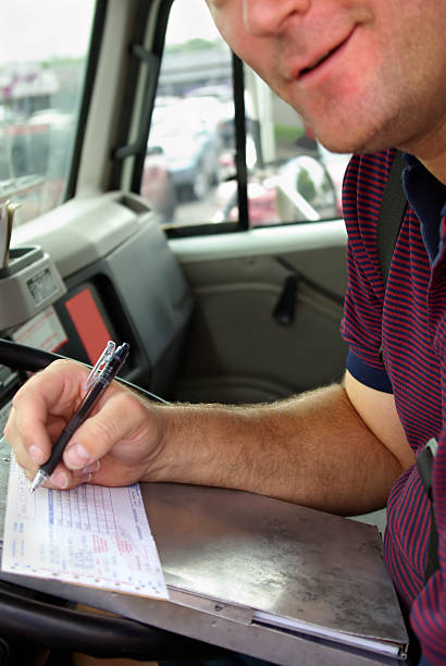 working man smiling while signing a receipt - mikefahl stock pictures, royalty-free photos & images