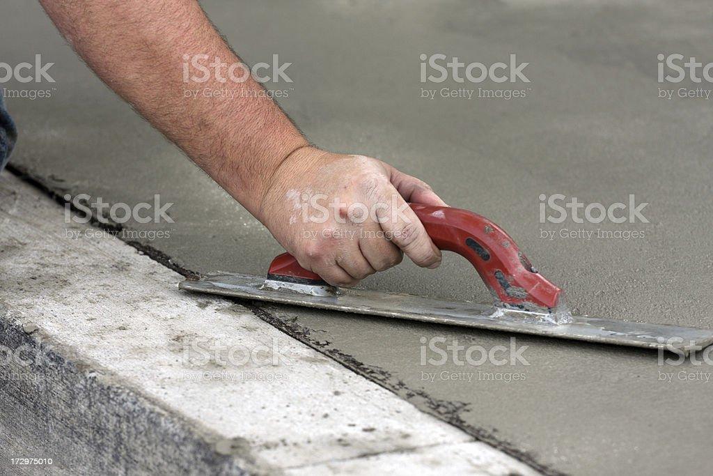 Working man troweling concrete stock photo
