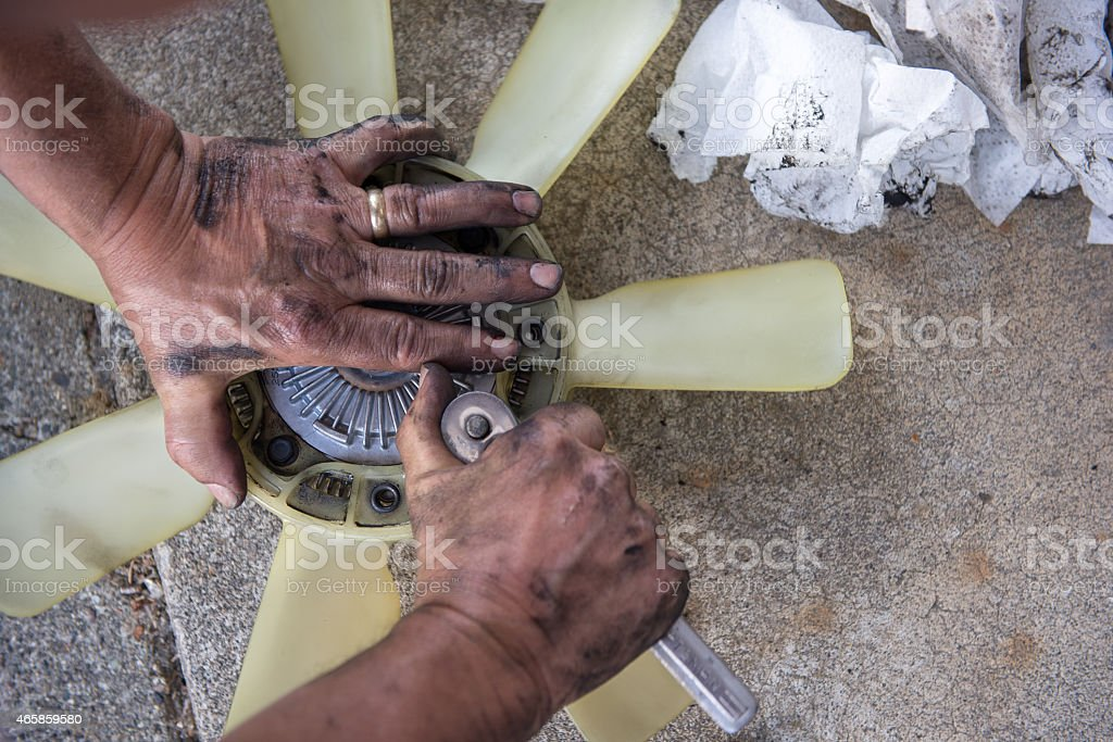 Working Man's Greasy hands fixing fan cluth. DIY stock photo