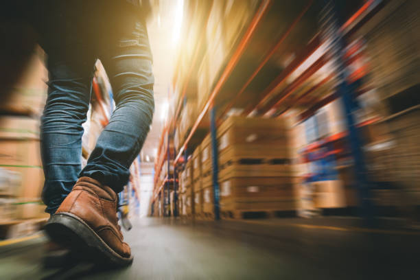Working men are walking to check the goods in stock. Working men are walking to check the goods in stock. warehouse stock pictures, royalty-free photos & images