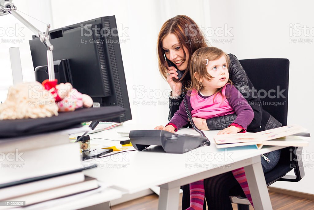 working mom and daughter at the office stock photo