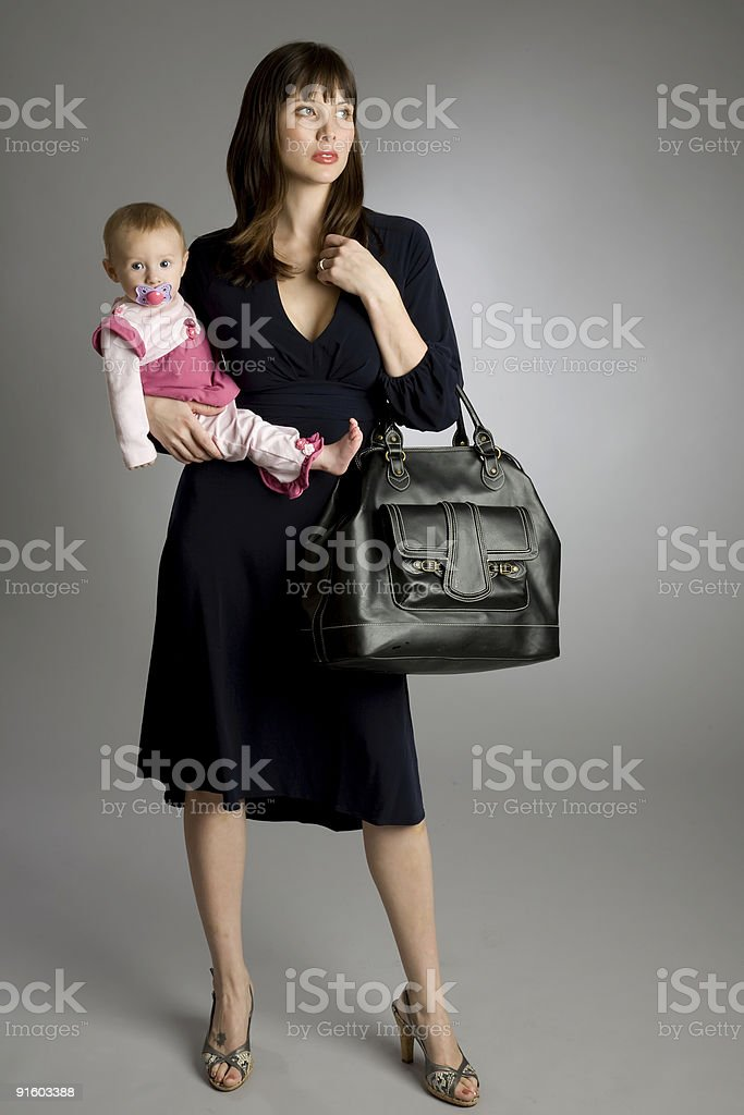 A working mom dressed in business attire holding her baby stock photo