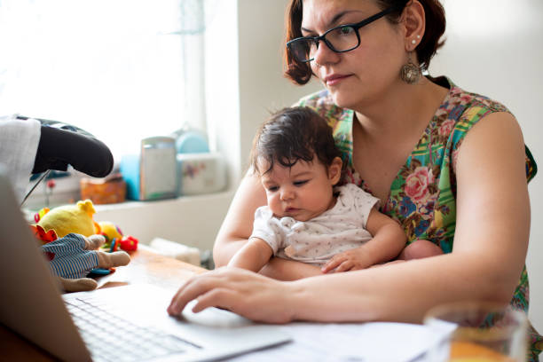 Working mom with baby in a lap stock photo