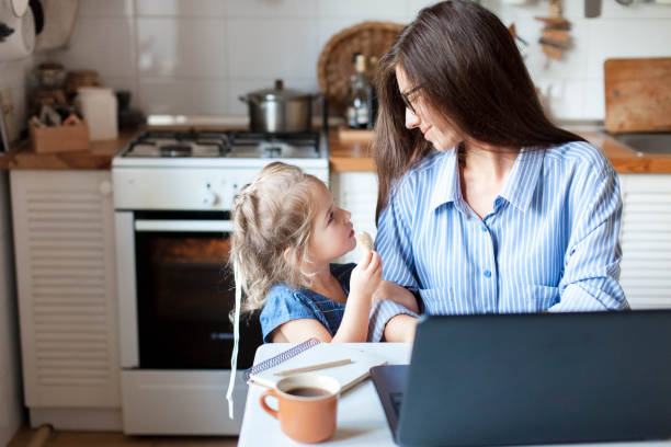 Working mom works from home office. Happy mother and daughter look to each other. stock photo