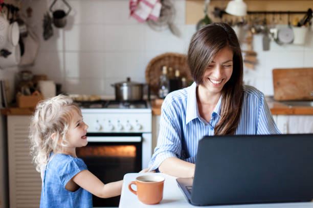 Working mom works from home office. Happy mother and daughter smiling. Successful woman stock photo