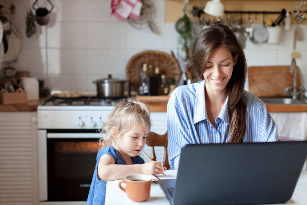 Working mom works from home office with kid. Happy mother and daughter. Woman and cute child stock photo