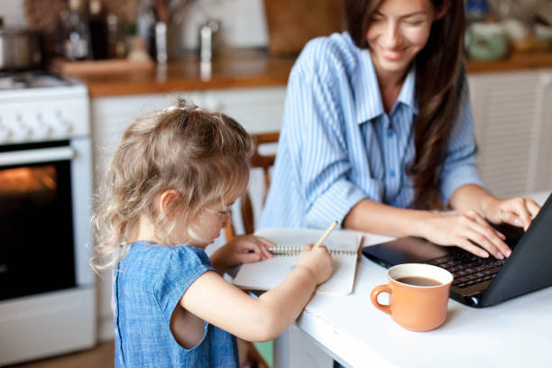 Working mom works from home office with kid. Happy woman using laptop. Cute child drawing stock photo