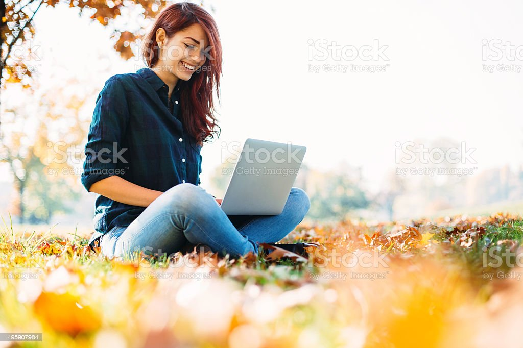 Working on a computer at autumn stock photo