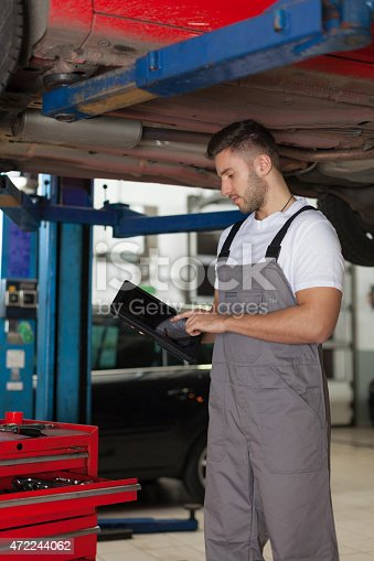 1137474295 istock photo Working on a Digital Tablet in Auto Repair Shop 472244062