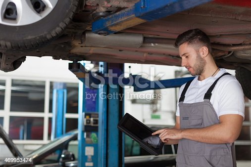 1137474295 istock photo Working on a digital tablet under the car 469953474