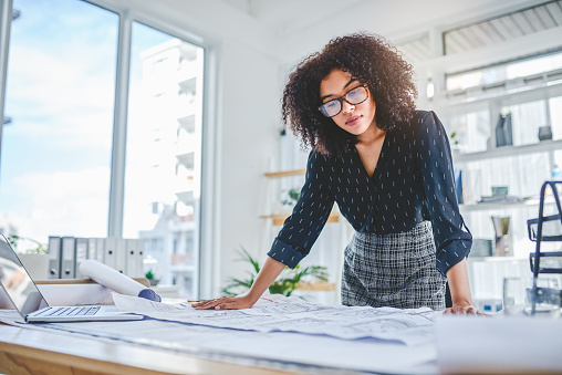 Shot of a young businesswoman working with blueprints in an office