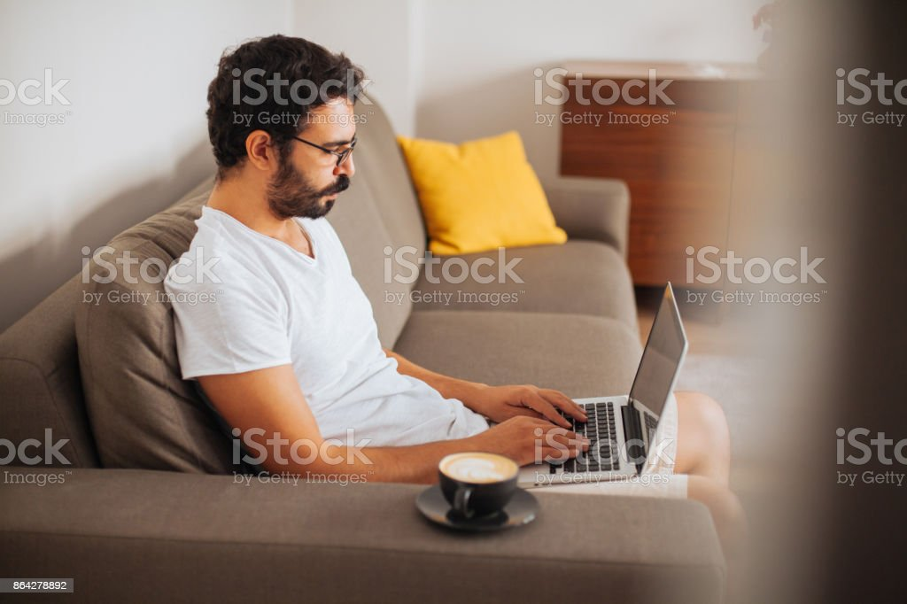 Working on a sofa with a laptop on his lap royalty-free stock photo