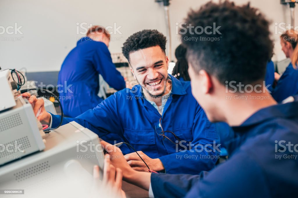Two mixed race engineering students work on a group project together...