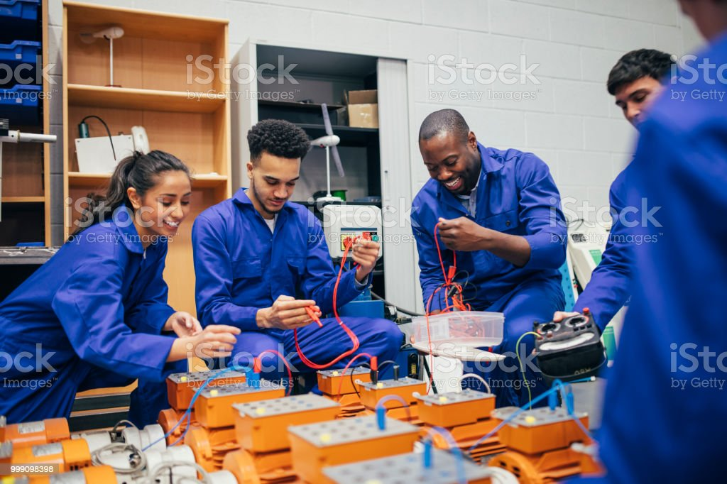 A group of engineering students and their tutor work on a group...