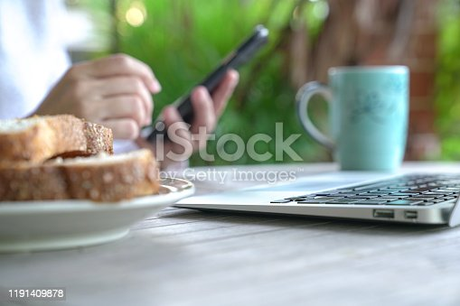 Working on the computer and cell phone while having breakfast. Work from home or flexi time concept.