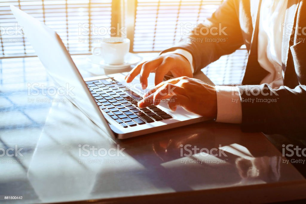 working on computer laptop online, closeup of hands of businessman stock photo