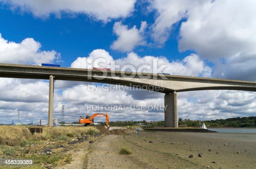 Ipswich, England - August 30, 2013: Construction workers building flood defences beneath the Orwell Bridge at Wherstead, near Ipswich, Suffolk, England. The River Orwell is tidal and can flood surrounding low-lying areas, particularly in the spring when tides are high. The Orwell Bridge carries the A14 road and was opened for traffic in late 1982.