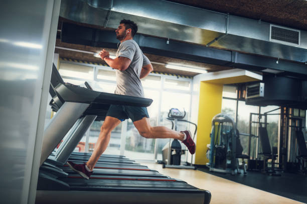Working on his condition Male running on treadmill at the gym training equipment stock pictures, royalty-free photos & images