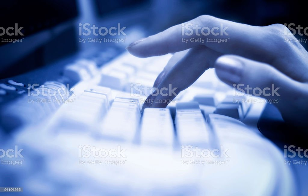 Working on keyboard with blue tint royalty-free stock photo