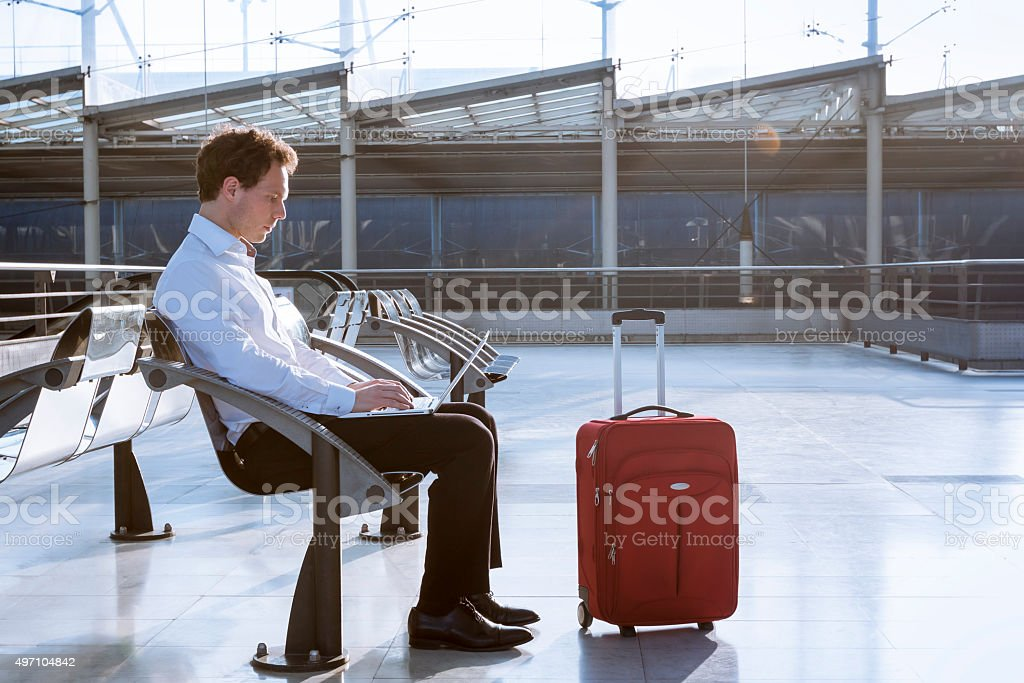 Working on laptop in airport while waiting for flight stock photo