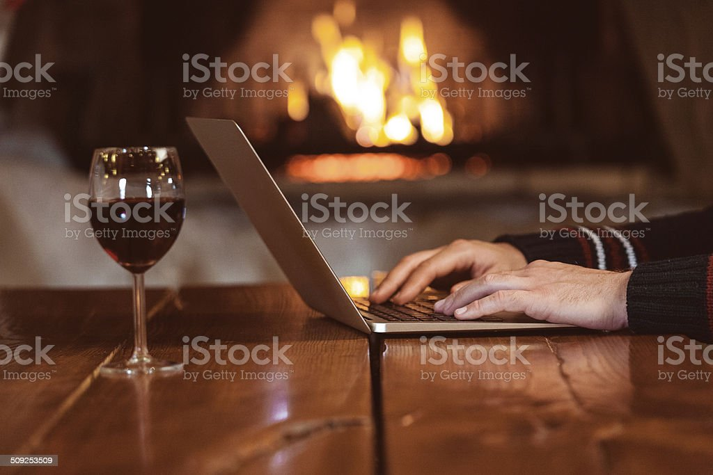 Working on laptop Man working on laptop at home with fireplace in the background. Close up of hands. Adult Stock Photo