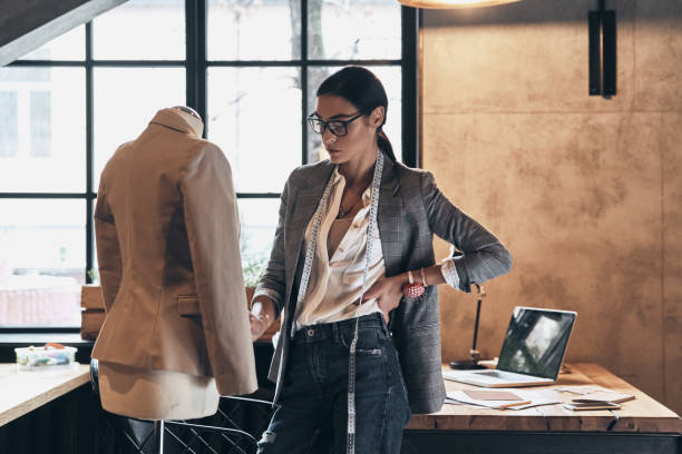 Working on new order. Serious young woman in eyewear keeping hand on hip and looking at mannequin while standing in her workshop fashion designer stock pictures, royalty-free photos & images