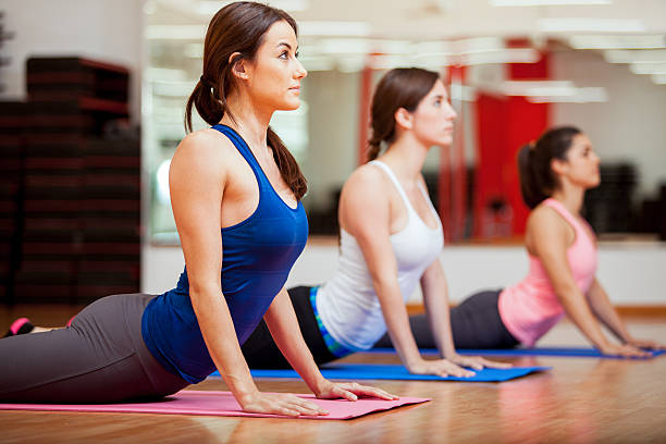 Working on the cobra yoga pose Cute Hispanic women practicing the cobra pose during their yoga class in a gym cobra pose stock pictures, royalty-free photos & images