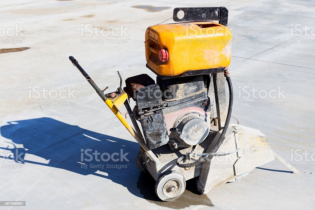 working on the road reconstruction. saw cutting asphalt with wat stock photo