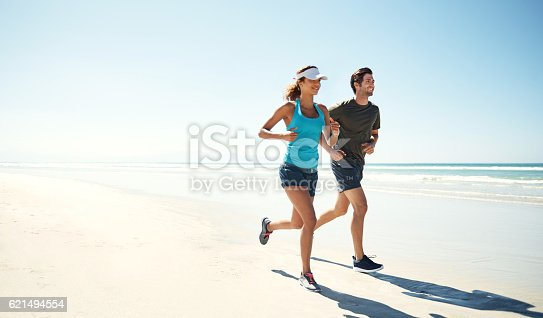 Shot of a young couple running along the beach together