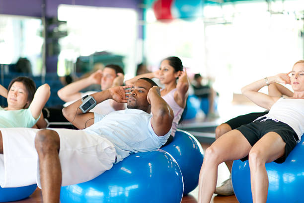 Working out Diverse group of people in gym doing exercise exercise class stock pictures, royalty-free photos & images