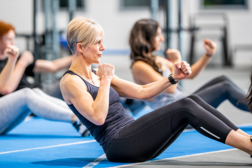 A middle aged caucasian woman shows a look of determination as she does an ab workout with a group of people in a gym.