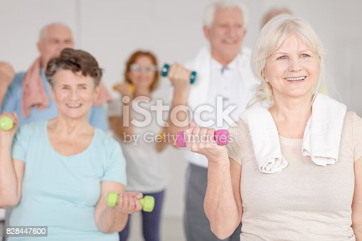 Elder happy people working out with colorful dumbbells