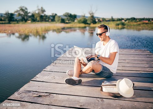 Young man sitting on the dock lake is working on laptop