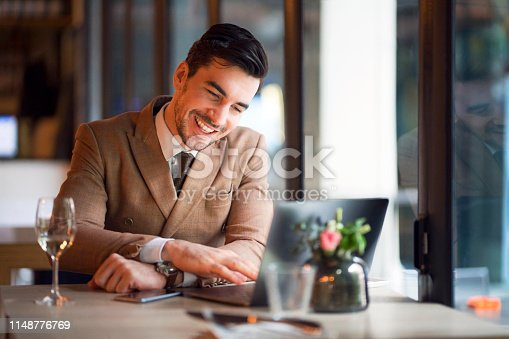 Handsome young Caucasian ethnicity businessman working on his laptop in upscale restaurant.