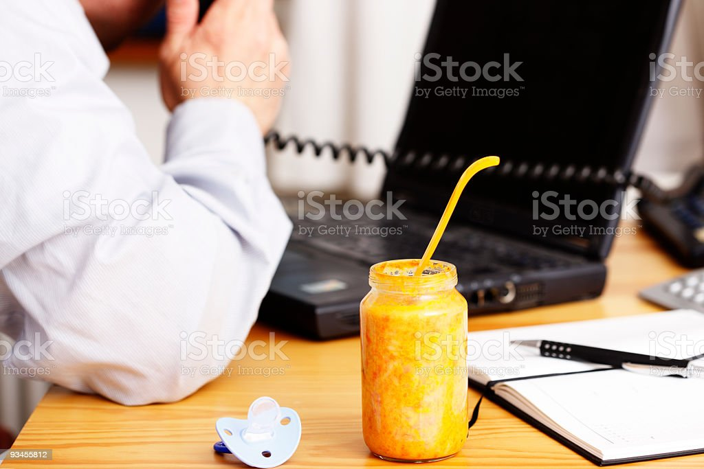 Working parent concept with baby food in the office stock photo