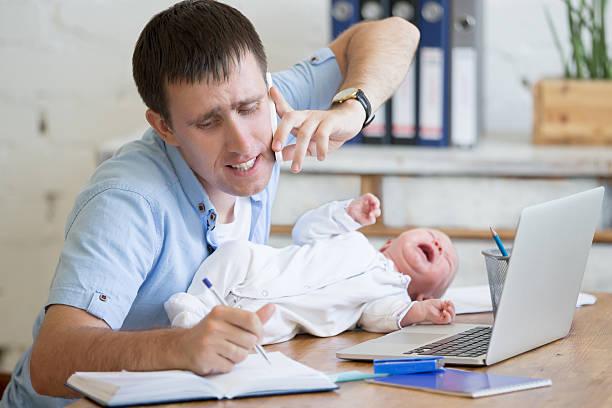 working parent with crying babe - papa humor stock-fotos und bilder