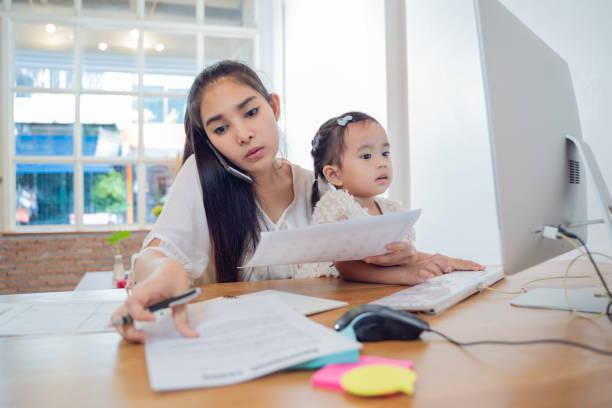 Padres trabajadores en casa, mujer asiática ocupada mamá trabajando con la hija en casa - foto de stock