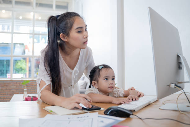 Padres trabajadores en casa,Busy Asian Woman mamá trabajando con hija en casa proteger de la infección de coronavirus o cóvide-19, pandemia, brote y epidemia de enfermedad - foto de stock