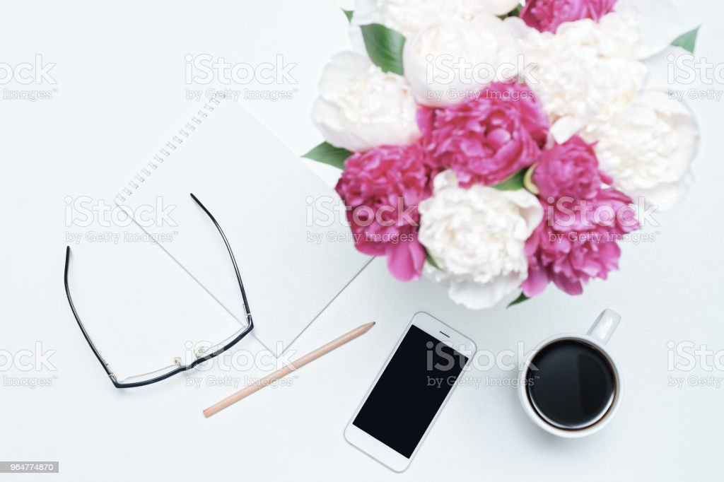 Working place glasses cup coffee mobile phone white pink peony royalty-free stock photo