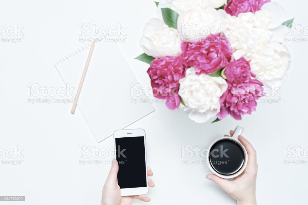 Working place hand cup coffee mobile phone white pink peony royalty-free stock photo