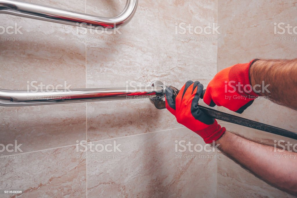 Working plumber mounts a new chrome-plated heated towel-type coil on the wall of tiles stock photo