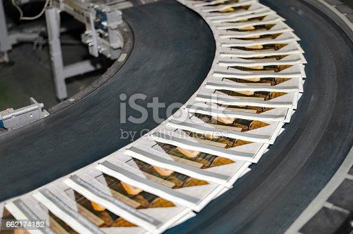 istock Working print machine with magazines on conveyor belt 662174182