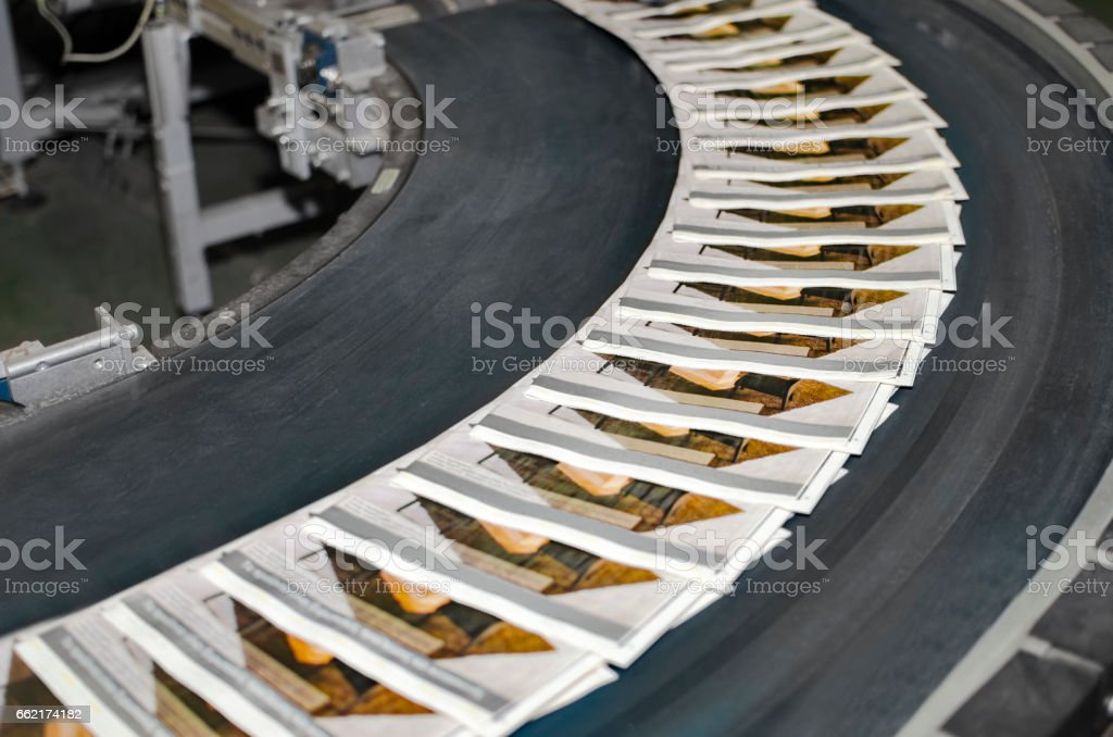 Working print machine with magazines on conveyor belt stock photo