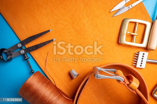 istock Working process of creating the leather belt in the leather workshop. Crafting tool, accessories, buckle and thread. Tannery atelier background. 1130393934