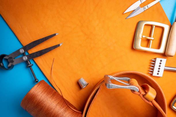 arbeitsprozess den ledergürtel in der lederwerkstatt zu schaffen. handwerk, werkzeug, zubehör, schnalle und thread. gerberei atelier hintergrund. - diy leder stock-fotos und bilder