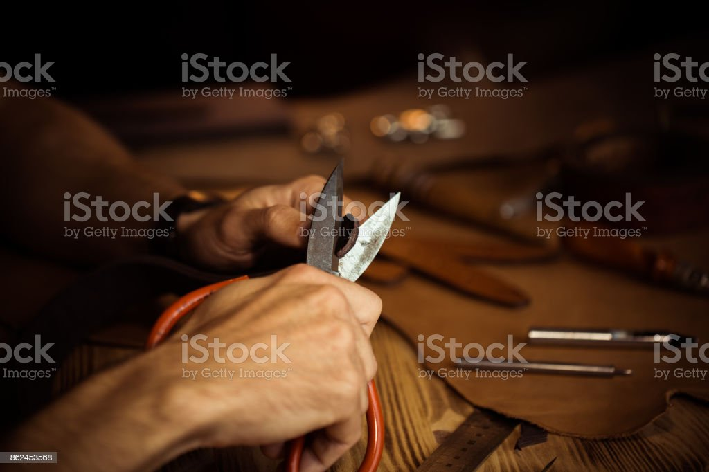 Working process of the leather belt in the leather workshop. Man holding crafting tool and working. Tanner in old tannery. Wooden table background. Close up man arm stock photo