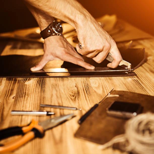 arbeitsprozess von der ledergürtel in der lederwerkstatt. mann handwerk werkzeug und arbeiten. tanner in der alten gerberei. holztisch hintergrund. mann arm hautnah. warmes licht für text und gestaltung - diy leder stock-fotos und bilder